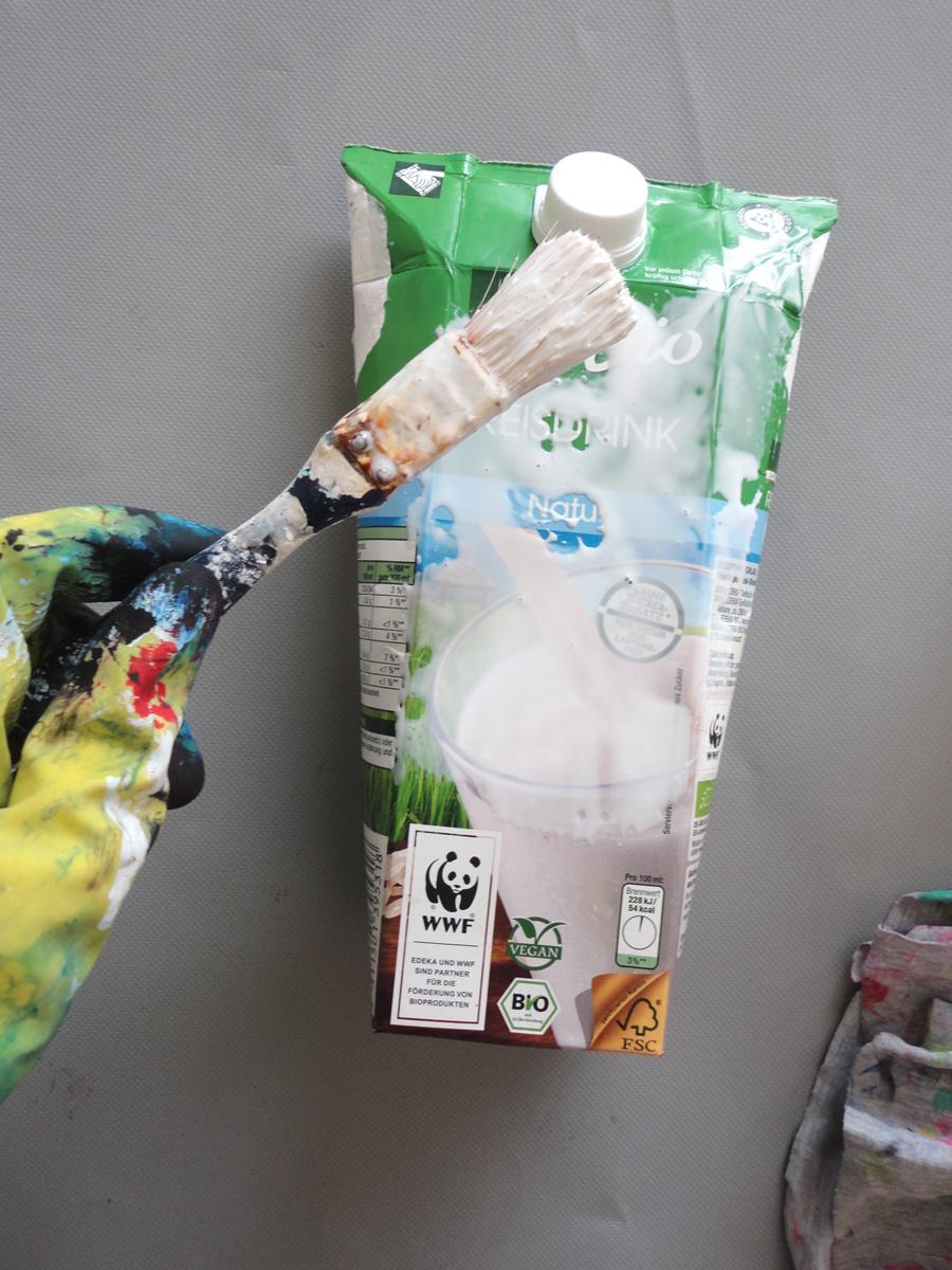 Milchkarton wird mit Leim eingestrichen