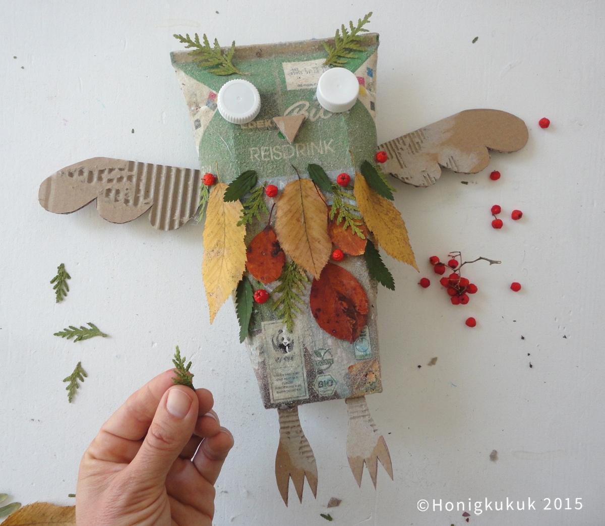 Eule wird mit bunten Blättern und Vogelbeeren beklebt